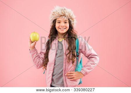 Small Happy Girl Earflap Hat Eat Apple. End Of Winter Semester. Holiday And Vacation. Kid Pink Backd
