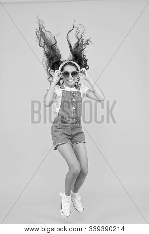 Set A Truly Energetic And Optimistic Mood. Energetic Little Girl With Long Brunette Hair Jumping On