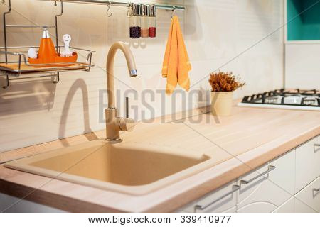 Designed Kitchen Beige Modern Faucet & Creamy Sink In Countertop. Beige Design Of Kitchen Countertop