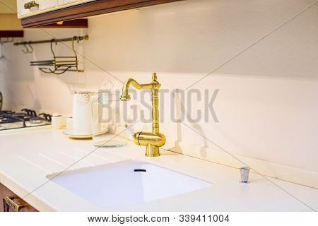 Designed Kitchen Golden Retro Faucet & White Sink In Creamy Countertop. Beige Design Of Kitchen Tile
