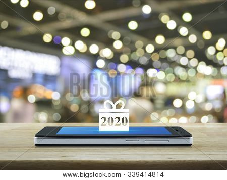 Gift Box Happy New Year 2020 Flat Icon On Modern Smart Mobile Phone Screen On Wooden Table Over Blur