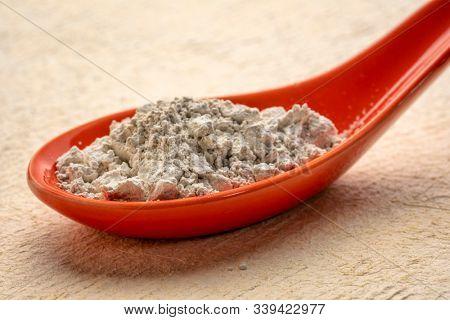 food grade diatomaceous earth detox supplement - red ceramic teaspoon of powder against rextured paper