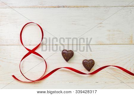 Red Gift Celebration Ribbon Waved In Shape Of Number 8 (eight) And Chocolate In Heart Shape On White