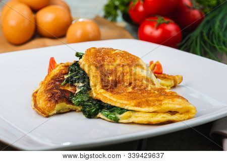 Traditional Omelet With Vegetables, Spinach, Tomatoes And Herbs On A Wooden Table In A Restaurant. C