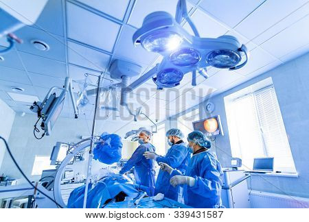 Medical Team Performing Surgical Operation In Bright Modern Surgery Room. Operating Theatre. Modern