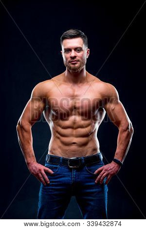 Muscular Guy With Naked Torso Posing With Hands On Waist. Studio Photo. Portrait Of A Handsome Man I
