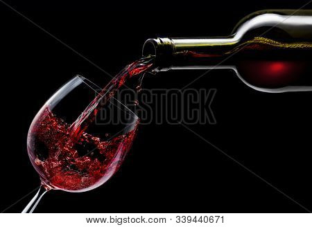 Red wine is poured into a wine glass on a black background.