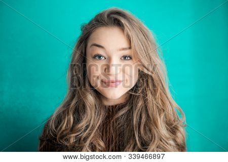 Beautiful young woman smiling in front of  a blue background.
