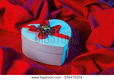 Valentines Greeting Card In Blue Light. White Cardboard Box In Shape Of Heart Wrapped In Ribbon Lay