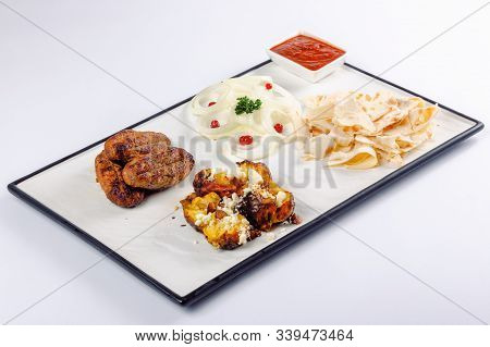 Kebab And Baked Potato With Cheese. Onion Circles And Pita Bread, Red Sauce On A White Board. Great