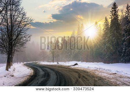 Country Road Through Forest At Sunset. Misty Winter Weather In Evening Light. Snow On The Roadside.