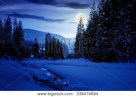 Frozen And Snow Covered Mountain River At Night. Carpathian Winter Landscape In Full Moon Light Ligh