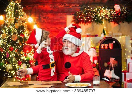 Christmas Helper Child Writing Letter To Santa Claus Letter In Red Hat. Kid And And Grandfather Writ