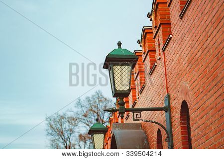 An Iron Lantern On A Brick Wall.