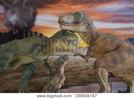 Family Of Tyrannosaurus Rex Dinosaurs With Erupting Volcano In The Background In Cretaceous Era