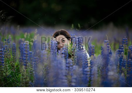 Crazy Funny Girl With Beautiful Smilie Hiding In Green Field With Many Flowers, Lupins In Summer. Hi