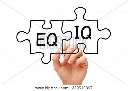 Hand Writing Eq And Iq On Jigsaw Puzzle With Black Marker On Transparent Wipe Board. Concept About T