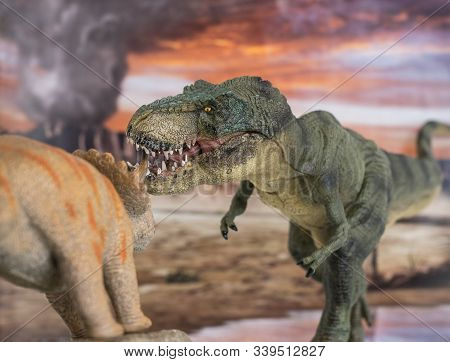 Tyrannosaurus Rex Fighting With A Triceratops With Erupting Volcano In The Background. Hard Fight In