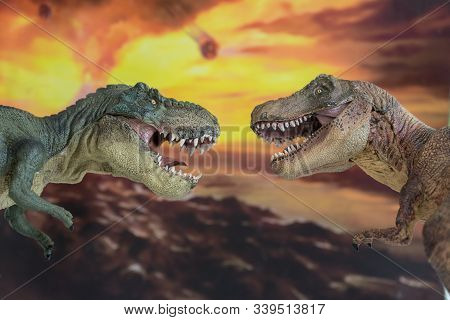 Couple Of Tyrannosaurus Rex Fighting In The Foreground With Erupting Volcano In The Background.