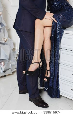 Handsome Man In Stylish Suit Bares Sexy Female Legs From A Luxury Evening Dress. Male And Female Sil