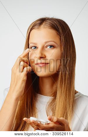 Young Woman Holds Contact Lens On Her Finger Over White Background. Eyewear, Eyesight And Vision, Ey