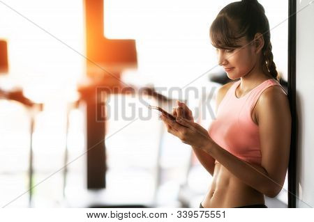 Asian Girl Relax After Workout In Fitness Center By Her Smart Phone, This Image Can Use For Gym, Sma