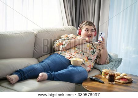 Asian Fat Girl Sleep On Sofa, Enjoy Eating A Fat Food And Relax By Music From Head Phone And Smartph