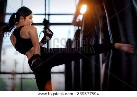 Asian Girl Kick A Sand Bag In Kickboxing Gym, This Image Can Use For Fitness, Sport, Exercise And Mu
