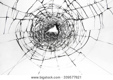 Cracks On Broken Glass. The Window Is Damaged By A Shot From A Firearm. Transparent Windscreen Of A