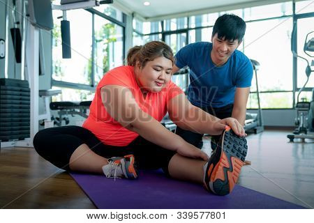 Asian Fat Girl Relax After Exercise With Ber Trainner In Fitness Center, This Photo Can Use For Diet