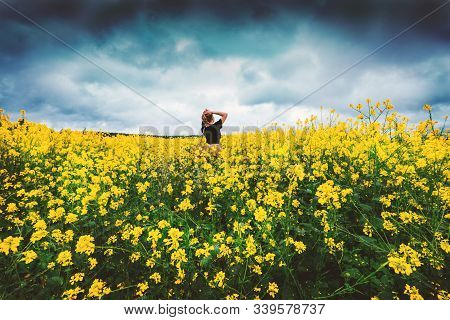 Happy Woman Rejoices Summer Walking On Meadow With Many Yellow Flowers. Young Lady Thinking About Li