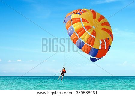 Parasailing On Tropical Beach In Summer. Flying Parachute With Man.