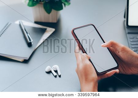 Close Up Of Man Hand Holding Smart Phone. Blank Screen Mockup For Graphics Display Montage.