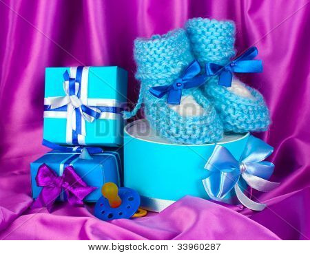 blue baby boots, pacifier, gifts on silk background