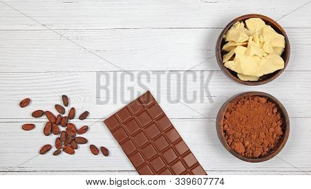 Bar Of Milk Chocolate, Cocoa Powder, Cocoa Butter And Cocoa Beans On Light Wooden Background. Top Vi