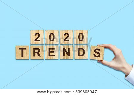 2020. Trends. Female Hand Makes Up Words From Wooden Blocks. Isolated On A Blue Background. New Year