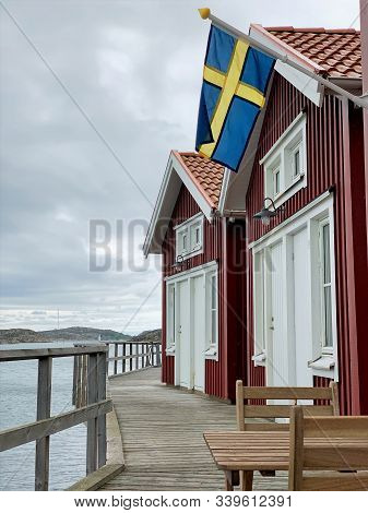Swedish Flag Seaside. The Flag Of Sweden On A Small Beach Cottages In The Seaside Town Skärhamn.