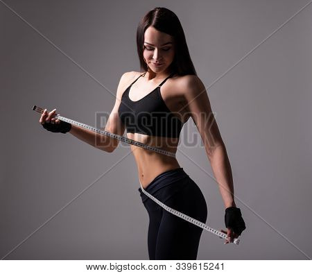 Beautiful Sporty Woman With Muscular Body Measuring Her Waistline With Measure Tape Over Gray Backgr