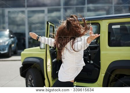 Young Woman In White Official Clothes Dancing In Front Of Hew New Green Automobile Outdoors.