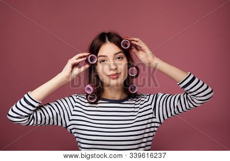 A Cute Tender Girl With Blue Eyes And Dark Hair In A Striped Sweater And Pink Curlers Clings To Her