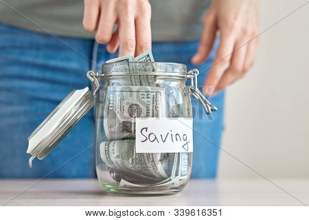 Woman Hand Holding Us Dollar Bill And Putting In A Glass Jar With Inscription Saving. Saving Money A