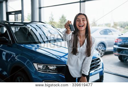 Excited With Her New Car. Holds Keys In Hand. Young Woman In White Official Clothes Stands In Front