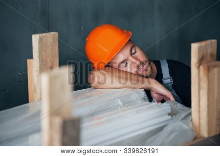 Sleeping On A Job. Taking A Break. Industrial Worker Indoors In Factory. Young Technician With Orang