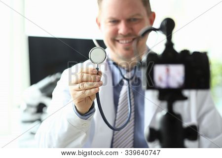 Focus On Male Hand Holding And Showing Stethoscope To Camera. Smiling Doctor Wearing White Medical G