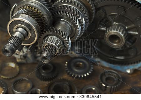 Gear Wheels, Damaged Modes Lie On A Wooden Table Top. In The Background A Manual Transmission From T