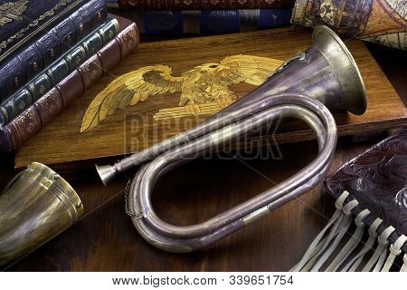 Old Antique Brass Bugle With Leather Books And Wooden Eagle.