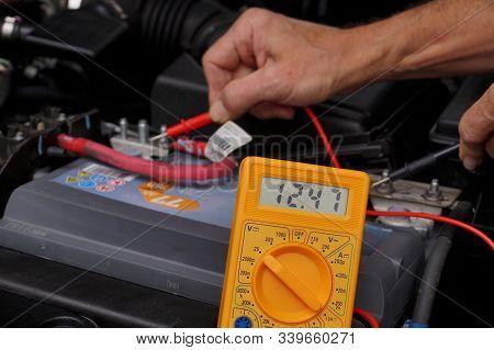 Battery Voltage Measurement With A Meter. Car Repair Shop.