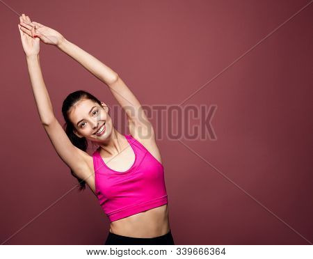 A Cheerful Thin European In A Sporty Pink Top And Black Leggings Extended Her Arms Up And Does Gymna