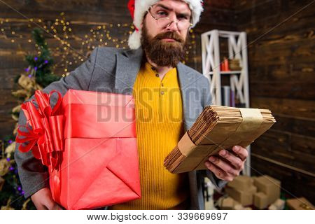 Post For Santa Claus. Man Bearded Hipster Wear Santa Hat Hold Bunch Of Letters And Gift Box. Man Mat