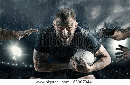Rugby football player in action on dark arena background
